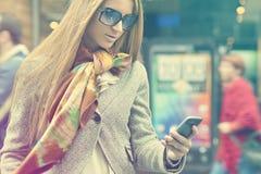 Vrouw die met smartphone op straat loopt Stock Afbeelding