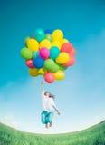 Vrouw die met stuk speelgoed ballons op de lentegebied springen Royalty-vrije Stock Afbeelding