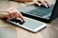 Vrouw die met tablet en laptop werken Stock Afbeeldingen