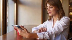 Vrouw die met tabletcomputor bij koffie werken stock footage