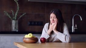 Vrouw die met tandpijn rode appel eten stock video