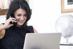 Vrouw die met telefoon en laptop werkt Royalty-vrije Stock Foto