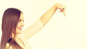 Vrouw die met vinger op exemplaarruimte richten Stock Foto's