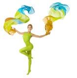Vrouw die met vliegende kleurrijke stof, witte achtergrond dansen Stock Fotografie