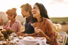 Vrouw die met vrienden bij openluchtdinerpartij genieten van stock afbeeldingen