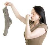 Vrouw die met vuile sok haar neus houdt Stock Afbeelding