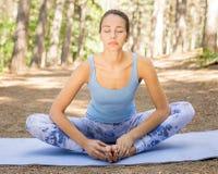 Vrouw die met zich ogen het gesloten uitrekken mediteren in openlucht doend yoga in park royalty-vrije stock foto's
