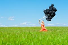 Vrouw die met zwarte ballons op het groene gras lopen Stock Afbeeldingen