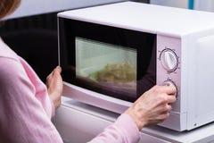 Vrouw die Microgolf Oven For Heating Food gebruiken royalty-vrije stock afbeelding