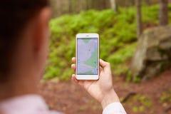 Vrouw die in midden zich nergens bevinden van, gebruikend navigatie app op smartphone, na route met hulp die van kaart, apparaat  stock foto