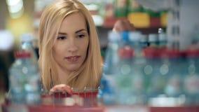 Vrouw die mineraalwater in kruidenierswinkelopslag kiezen stock footage