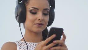 Vrouw die mobiele cel slimme telefoon op strand met behulp van die oortelefoons voor muziek dragen of Meisje in bikini spreken di stock videobeelden
