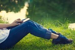 Vrouw die mobiele slimme telefoon op de benen in groen gras en meer met behulp van royalty-vrije stock fotografie
