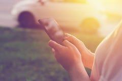 Vrouw die mobiele telefoon app met behulp van aan de cabine van de vraagtaxi Royalty-vrije Stock Afbeeldingen