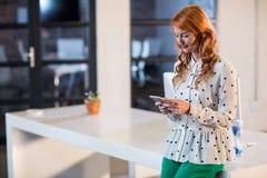 Vrouw die mobiele telefoon in bureau met behulp van stock afbeelding