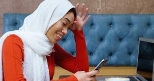 Vrouw die mobiele telefoon in cafetaria 4k met behulp van stock footage
