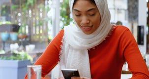 Vrouw die mobiele telefoon in cafetaria 4k met behulp van stock videobeelden