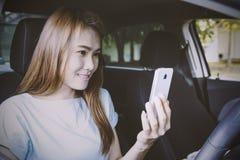 Vrouw die mobiele telefoon in de auto met behulp van Stock Afbeeldingen
