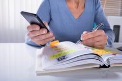 Vrouw die Mobiele Telefoon met Agenda met behulp van royalty-vrije stock foto's