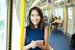Vrouw die mobiele telefoon in metro compartiment met behulp van stock afbeeldingen