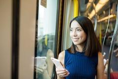 Vrouw die mobiele telefoon in metro compartiment van Hong Kong met behulp van royalty-vrije stock foto