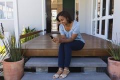 Vrouw die mobiele telefoon op de portiek thuis met behulp van stock foto