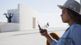 Vrouw die mobiele telefoon op dijk met behulp van stock videobeelden