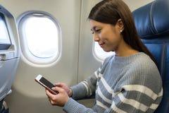 Vrouw die mobiele telefoon in vliegtuigcabine met behulp van Stock Foto's