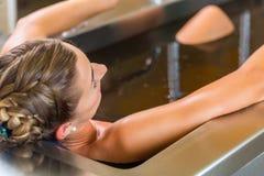 vrouw die modderbad van alternatieve therapie genieten royalty-vrije stock afbeeldingen