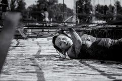 Vrouw die in modderlooppas en hinderniscursus worstelen stock afbeelding