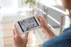 Vrouw die moderne kabeltelevisie-camera's op smartphone binnen controleren royalty-vrije stock afbeeldingen