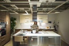 Vrouw die moderne luxekeuken kopen stock afbeeldingen