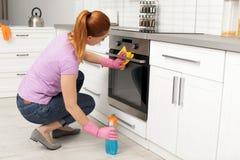 Vrouw die moderne oven met vod en detergens schoonmaken royalty-vrije stock afbeelding