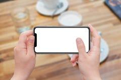 Vrouw die moderne slimme telefoon in horizontale positie houden Stock Afbeelding