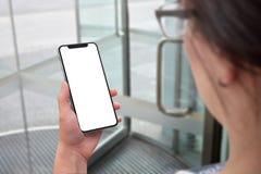 Vrouw die moderne slimme telefoon met het geïsoleerde x gebogen scherm voor model houden Stock Afbeelding