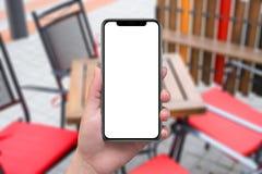 Vrouw die moderne zwarte slimme telefoon met x gebogen randen houden Stock Foto's