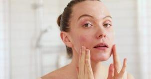 Vrouw die moisturiser op haar gezicht in spiegel van toepassing zijn stock video