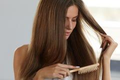 Vrouw die Mooi Gezond Lang Haar met Borstelportret borstelen Stock Fotografie