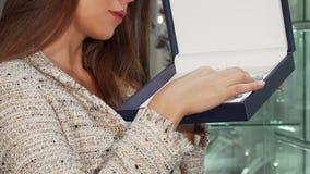 Vrouw die mooie halsband in een juwelendoos onderzoeken, die bij de juwelenopslag winkelen stock video