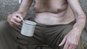 Vrouw die muntstuk geven aan dakloosheid stock footage