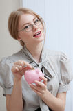 Vrouw die muntstuk opnemen in een spaarvarken Royalty-vrije Stock Foto's