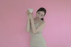 Vrouw die muntstuk in spaarvarken zet stock fotografie