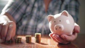 Vrouw die muntstuk in spaarvarken zetten, die geldconcept bewaren Het het toekomstige onderwijs of hypothecaire krediet van de be stock video