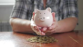 Vrouw die muntstuk in spaarvarken zetten, die geldconcept bewaren Het het toekomstige onderwijs of hypothecaire krediet van de be stock footage