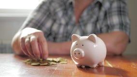 Vrouw die muntstuk in spaarvarken zetten, die geldconcept bewaren Het het toekomstige onderwijs of hypothecaire krediet van de be stock videobeelden