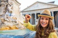 Vrouw die muntstuk tonen dichtbij fontein van het pantheon Stock Foto