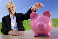 Vrouw die Muntstuk zet in Roze Spaarvarken stock foto