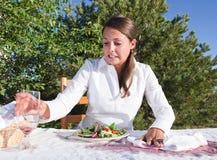 Vrouw die na het morsen van wijn probeert schoon te maken stock foto