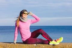 Vrouw die na in openlucht het doen van sporten op koude dag rusten Royalty-vrije Stock Afbeelding