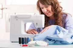 Vrouw die naaimachine met behulp van Stock Foto